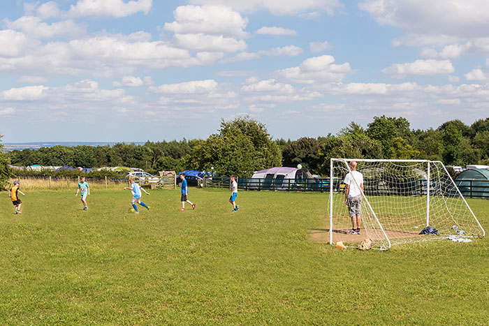 children enjoying the onsite football pitch at Golden Square Caravan Park