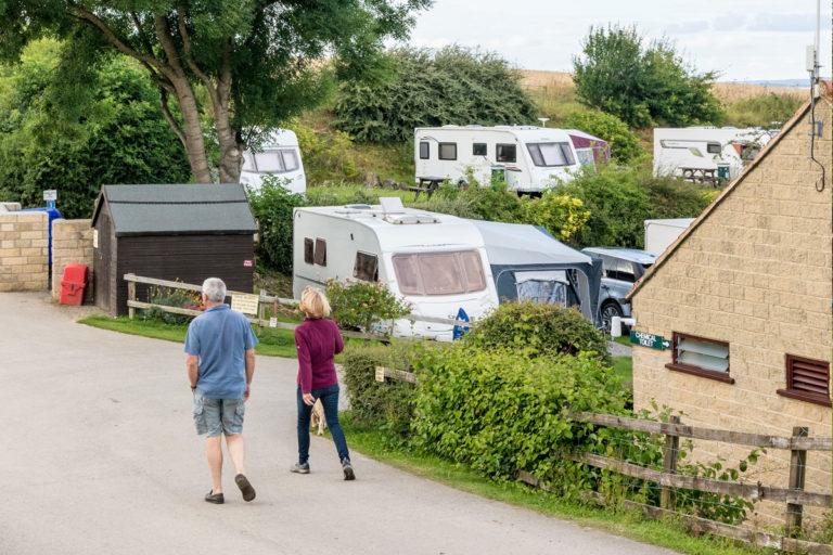 couple walking through Golden Square touring caravan site